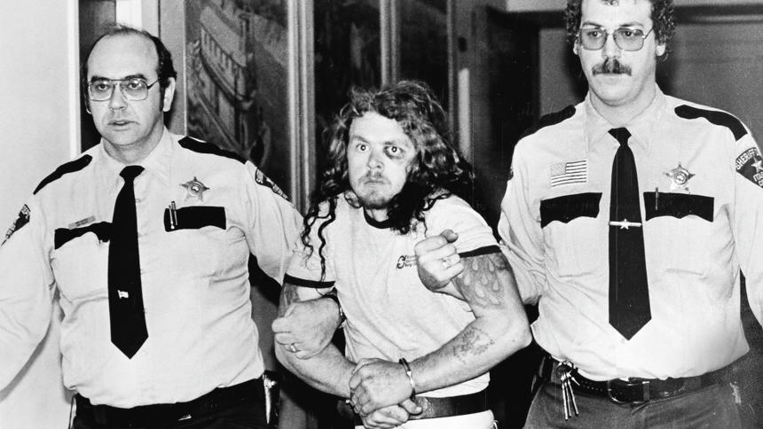 """1981 Duluth News Tribune file -- PAROLE1226c3 -- Audie L. Fox, then 27, of Pengilly, Minn., is led from the Itasca County Courthouse on Nov. 2, 1981, after being arraigned on charges of first-degree murder in hte slaying of Itasca County Deputy Robert """"Beefy"""" Lawson. Escorting Fox is Chief Deputy Robert Serich (left) and Deputy Steve Hurst."""