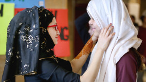 t4.7.16 Bob King -- kingHIJAB0408c1 -- Azrin Awal helps Sarina Men put on a hijab Thursday during Hijab Day at UMD. Anyone who wanted could stop by to try on a hijab or Muslim prayer cap as part of Islamic Awareness Week. Bob King / rking@duluthnews.com