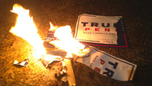 Donald Trump campaign signs taken from donors leaving an event Friday, Aug. 19, 2016, burn on the sidewalk in front of the Minneapolis Convention Center. (Pioneer Press: Jaime DeLage)