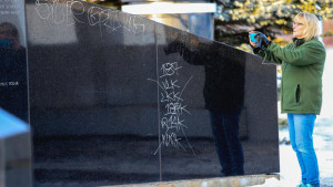 t011717 --- Clint Austin --- 011817.N.DNT.VANDALISM.CO1 --- Kathleen Wolleat of Duluth pauses to take a picture of the reflection of the Aerial Lift Bridge on the granite of the Vietnam Veterans Memorial on Duluth's Lakewalk Tuesday afternoon. Wolleat was disappointed that she had to work around graffiti that was drawn all over the monument with a paint pen. (Clint Austin / caustin@duluthnews.com)