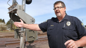 t5.4.15 Bob King -- kingRAILSAFE0614c1 -- Proctor police chief Walter Wobig stands by a rail crossing as he talks about Proctor's emergency readiness in the event of an incident at the Canadian National railyard. Bob King / rking@duluthnews.com