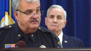 Grand Rapids Police Chief Scott Johnson tells repoters on Wednesday, Oct. 12, 2016, that a Minnesota council he will help lead will look into how law enforcement officers and community members can better trust each other. Gov. Mark Dayhton is in the background.(Forum News Service photo by Don Davis)