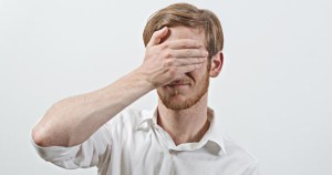 Young Adult Male Wearing White Shirt  Covers His Face by Hand, Gesturing He Has Made a Big Mistake