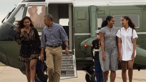 TOPSHOT - US President Barack Obama, First Lady Michelle Obama and daughters Malia and Sasha walk to board Air Force One at Cape Cod Air Force Station in Massachusetts on August 21, 2016 as they depart for Washington after a two-week holiday at nearby Martha's Vineyard. / AFP / NICHOLAS KAMM        (Photo credit should read NICHOLAS KAMM/AFP/Getty Images)